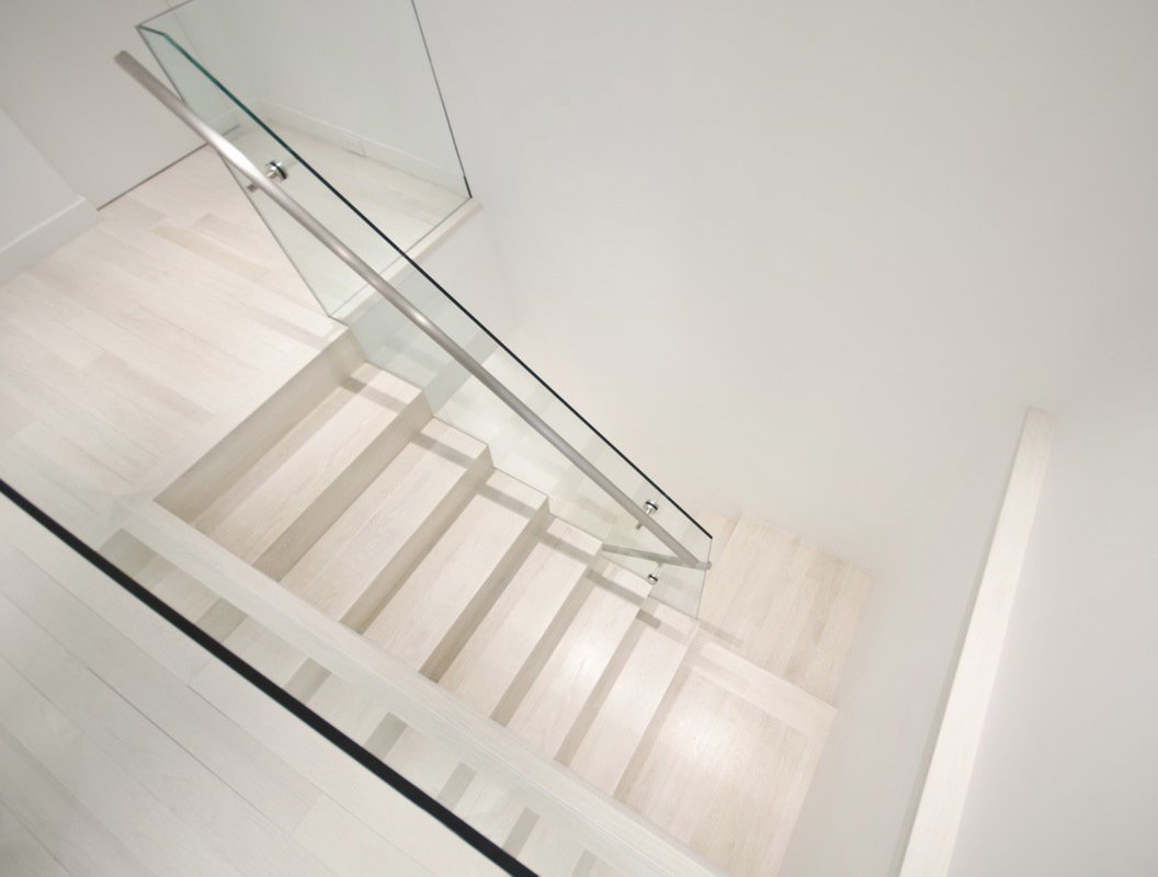 A stairwell featuring stainless-steel hand rails and glass connects the two levels.  University Place Apartment by Diana Budds