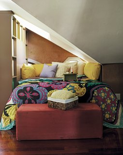 This top floor loft space in Atlanta has uneven ceilings and no walls, so Schuneman sectioned off a nook for her bed using a tall bookcase. Photo courtesy of: Random House, Inc.
