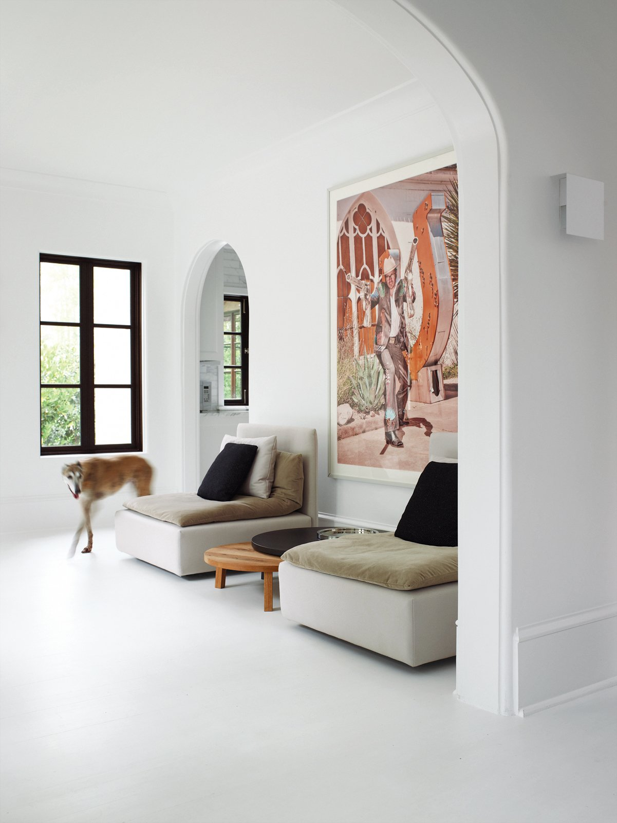 """Living Room, Chair, Coffee Tables, and Painted Wood Floor Two pieces from E15's Shiraz sofa flank   the company's wooden Leila side tables.   Hill chose to use flat paint in Benjamin Moore's Decorators White throughout the home   because it emphasizes the chalkiness of the plaster walls, making them """"look almost like slate."""" The sconce shown in the foreground—David Chipperfield's Corrubedo design for   FontanaArte—gives off a soft glow and   replaces the dozens of paper-lampshade   wall fixtures the owners found in the house when they bought it. Stewart Cohen's   zany photograph of a gun-toting Marfa   resident encapsulates Barbara Hill's offbeat brand of decorating: bright and minimal,   yet darkly humorous.  Living Areas from A Designer Brings Her Bold Brand of Texas Modern to this Atlanta Family Home"""