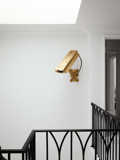 The gold (nonfunctioning) surveillance camera by artist Camp Bosworth in the stairwell previously hung in the glass entryway of the family's former house in Houston.