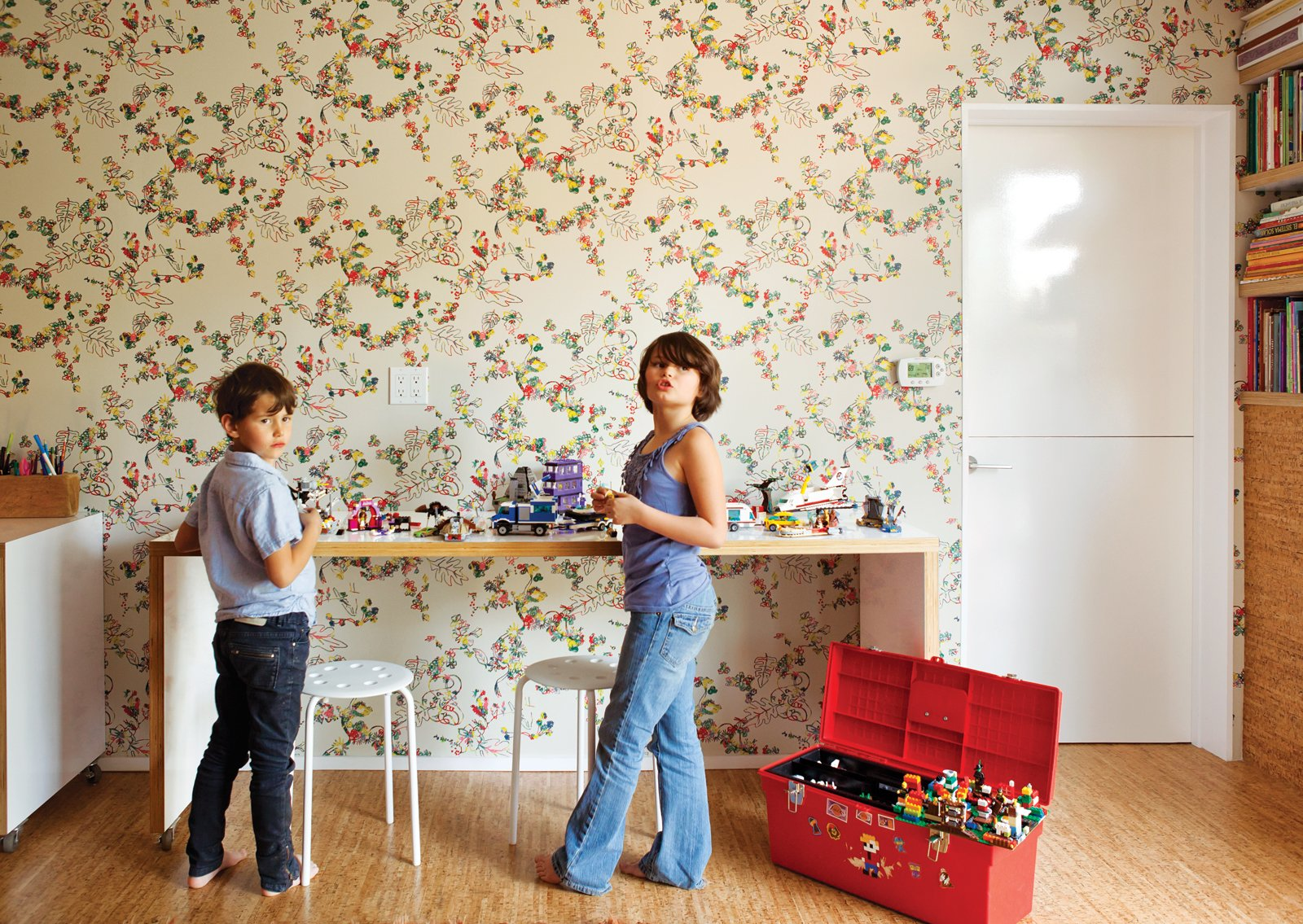 Kids, Medium Hardwood, Bookcase, Playroom, Neutral, Desk, and Pre-Teen Simon and Eva Luna play in front of a wall covered in Daks wallpaper from Walnut.  Kids Desk Neutral Photos from Wallpaper That Fixes Walls
