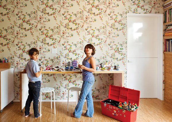 Simon and Eva Luna play in front of a wall covered in Daks wallpaper from Walnut.