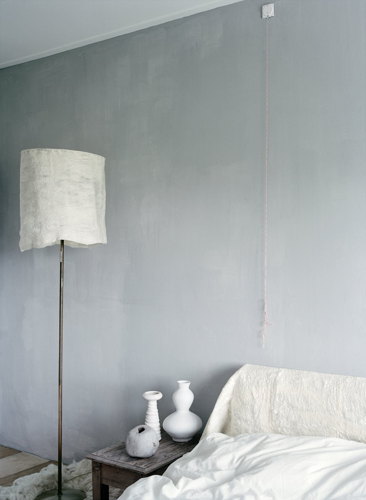 The couple's bedroom is a serene space with tinted plaster walls and a white felt headboard and lampshade by Leen.  Bedrooms by Dwell