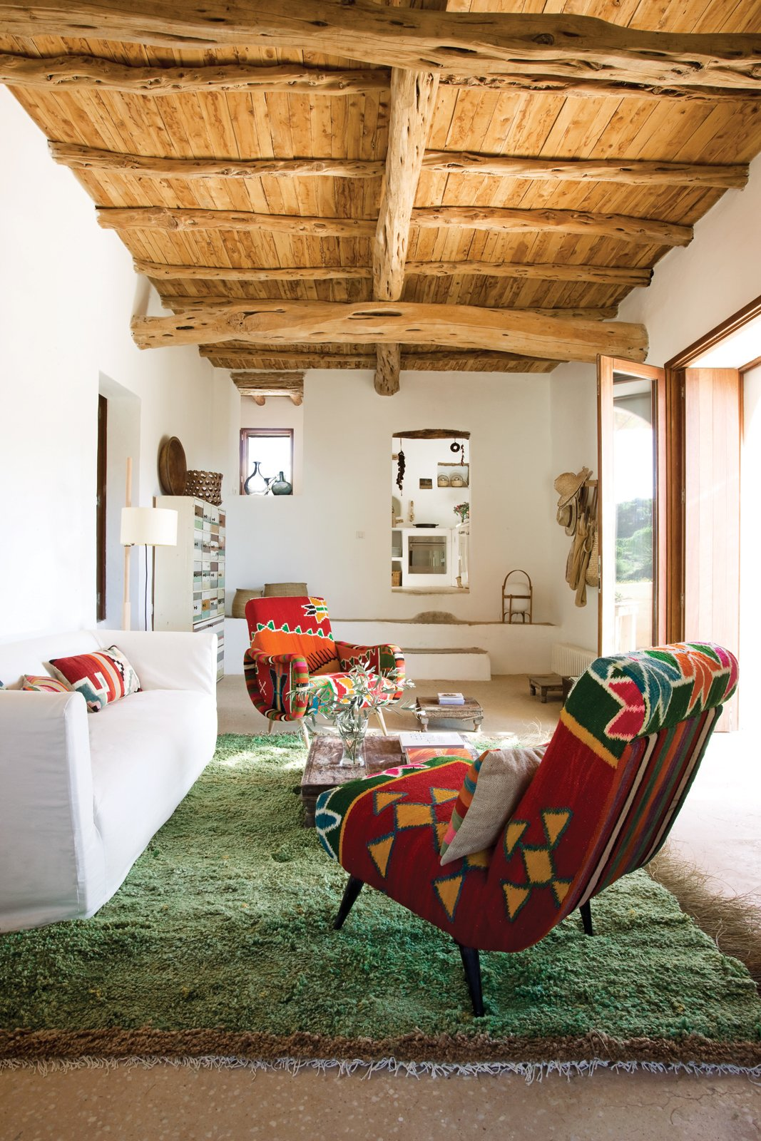 Living Room, Chair, and Sofa In Marquina and Font's living room, a pair of kilim-covered chairs by Philippe Xerri, a chest of drawers by Piet Hein Eek, and a handmade Tunisian rug provide bursts of color amidst the overall scheme of white, ecru, and cream.  Best Photos from This Designer Escapes to Ibiza for Some Peace and Quiet