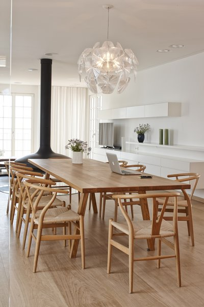 "The interior scheme prevents clutter in a variety of creative ways, including concealing a heat pump in the walls and installing flush-fitting LED spotlights. The architects explain, ""Since the redesign, the prevailing impression is one of spaciousness, the suffusion of light and simple elegance.""  A statement-making Hope Suspension Light by Luceplan is an elegant addition to the living area. The table, which was designed by the architects and fabricated by VHB Memmingen, is surrounded by CH24 Wishbone Chairs by Hans Wegner for Carl Hansen & Son."