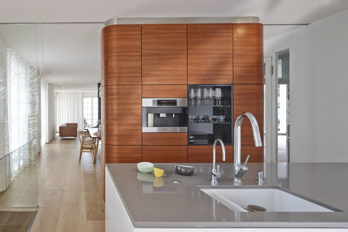 Kitchen, Wall Oven, Light Hardwood Floor, and Undermount Sink The kitchen features Miele and Bosch appliances surrounded by oak flooring from Bois Ditton; the shelves are walnut.  Best Photos from A Renovated Modernist Oasis in the French Riviera That Has Hosted Picasso and Royalty