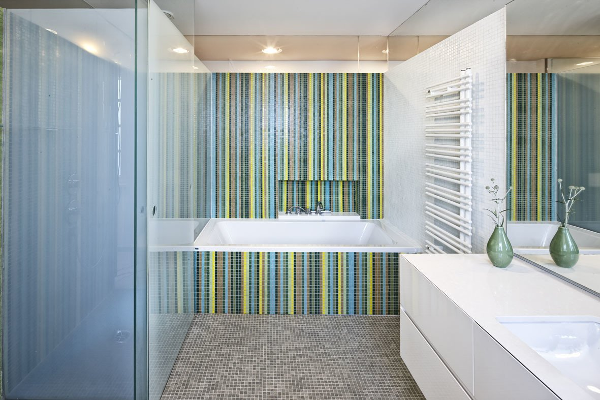 Bath Room, Drop In Tub, Mosaic Tile Wall, and Ceramic Tile Floor Glass elements not only allude to the ocean, but also lend a fresh look to some of the rooms. Here, Trend glass mosaic tiles brighten up the bathroom. Axor fixtures from Hansgrohe stand next to a minimalist radiator from Zehnder.  Photo 6 of 9 in A Renovated Modernist Oasis in the French Riviera