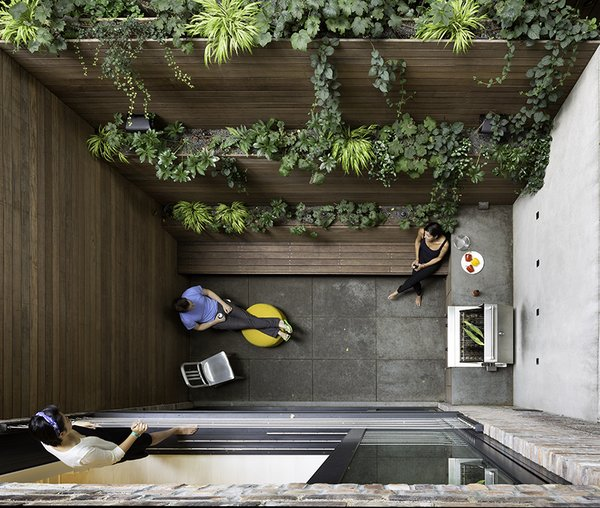 Even a small patio can have a monumental effect. A green wall in this kitchen patio also brings views to the higher parts of the slender town house, located in the West Village in New York. The counter and floor, clad in gray honed slate, and the teak-clad walls and bench complement the greenery.
