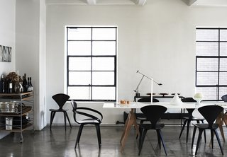 Metal-framed windows stand out against the white walls in this loft. Black Cherner chairs and a white table continue the motif.
