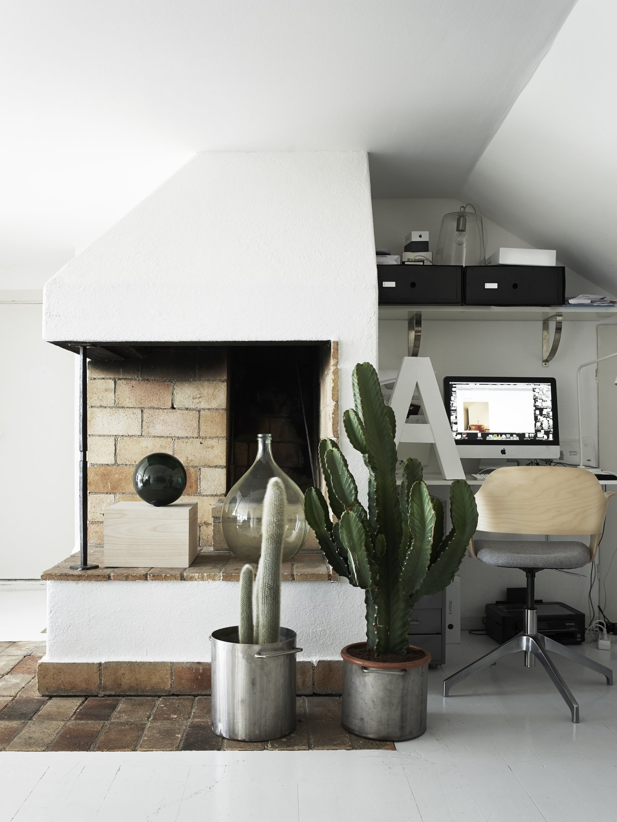 "Living Room and Standard Layout Fireplace Blogger and stylist Annaleena Leino Karlsson has designed her 1950s farmhouse to have a mostly white interior. Her workspace is next to a rustic brick and stucco fireplace, which is adorned with cacti and decorative objects.  Search ""11plus world desk clock"" from Monochromatic Color Palettes Are the Ultimate Modern Design Tool"