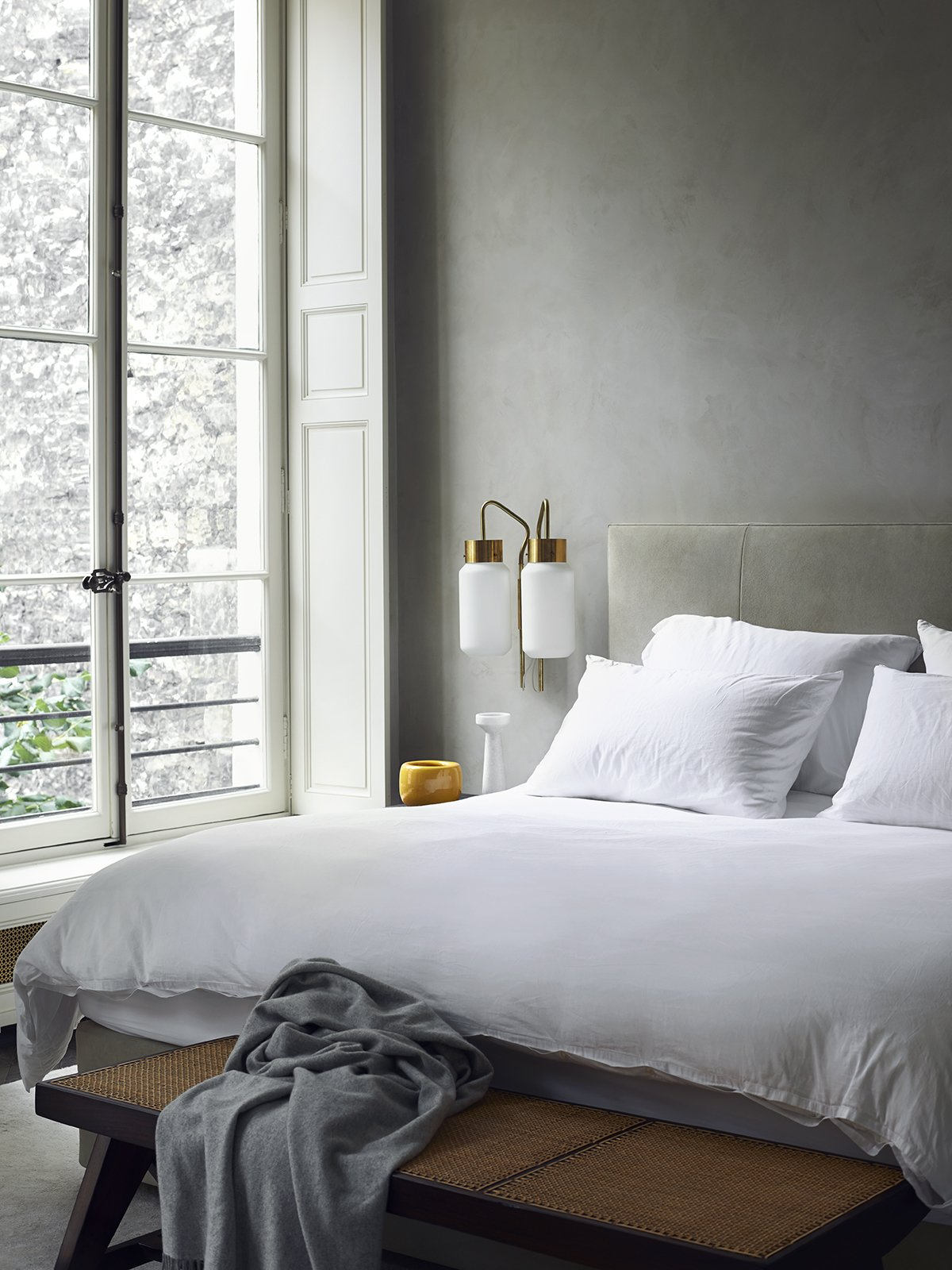Bedroom, Bench, Bed, and Wall Lighting Architect Joseph Dirand's bedroom boasts sandy gray walls and upholstered headboard. The white bed linens help reflect daylight into the space and the Azucena sconces offer task illumination.  Monochromatic Color Palettes Are the Ultimate Modern Design Tool by Diana Budds