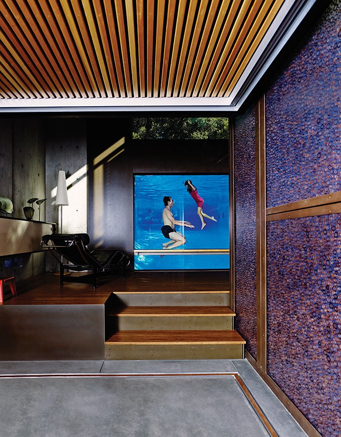 Living Room, Floor Lighting, Lamps, Dark Hardwood Floor, Chair, Concrete Floor, and Storage Spencer Greene and his daughter, Anya, go for a dip in their Palo Alto, California, home. The three-inch-thick acrylic pool window allows the parents to monitor their children's swims from the LC4 chaise longue.  Shining Examples of Clerestory Windows by Luke Hopping from This House Doesn't Hold Back on Colorful Details