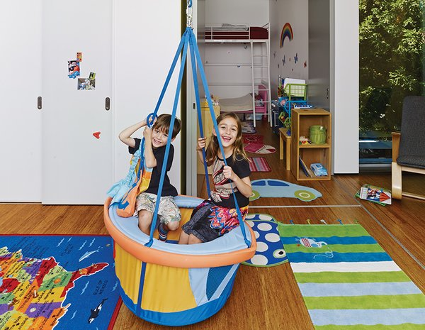 In their bedroom, Anya and Yash hang out in the boat-shaped swing by Haba that their aunt brought them from Germany (it's not currently available in the United States). A Rapson Rapid Rocker by Rapson-Inc. sits next to the window.