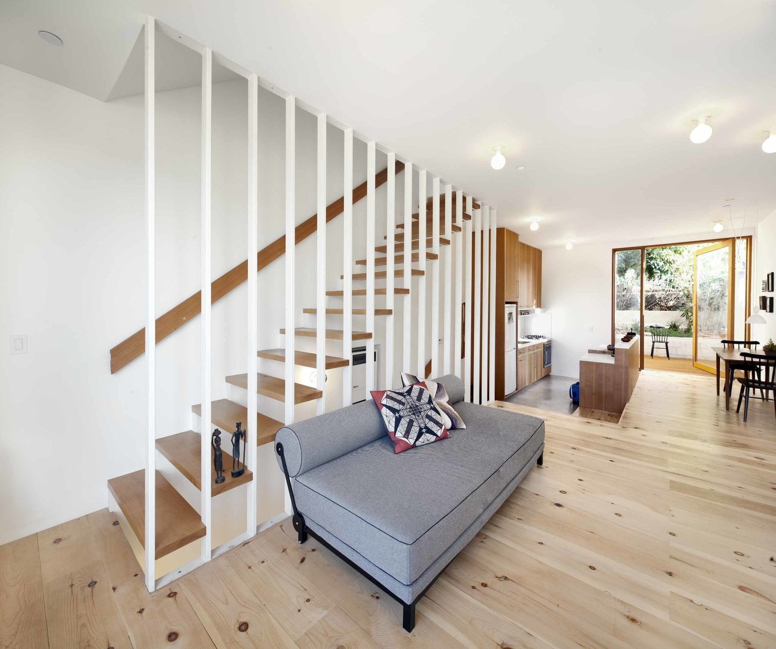 """The first floor contains the living room and kitchen, which opens out onto a petite back garden and an avocado tree. The kitchen is slightly sunken and has a polished concrete floor, which subtly demarcates it from the rest of the space. Materials in the kitchen set the home's material palette, with vertical Douglas fir cabinets and the same 3"""" x 6"""" subway tiles that appear in the bathroom for the backsplash. The Fisher & Paykel dishwasher is hidden inside the island: """"I wanted the island to look more like a credenza or piece of furniture,"""" says Storey.  The wood floor boards in the living room are white pine, a soft wood Storey chose for its knotty look. """"The wood dries a lot over time, so small gaps have opened up between them. Because it's such a simple white space, it's nice to have that rough warmth and character in the floors.""""  Photo 2 of 9 in Home and Studio Maximizes Very Narrow Site in Echo Park"""