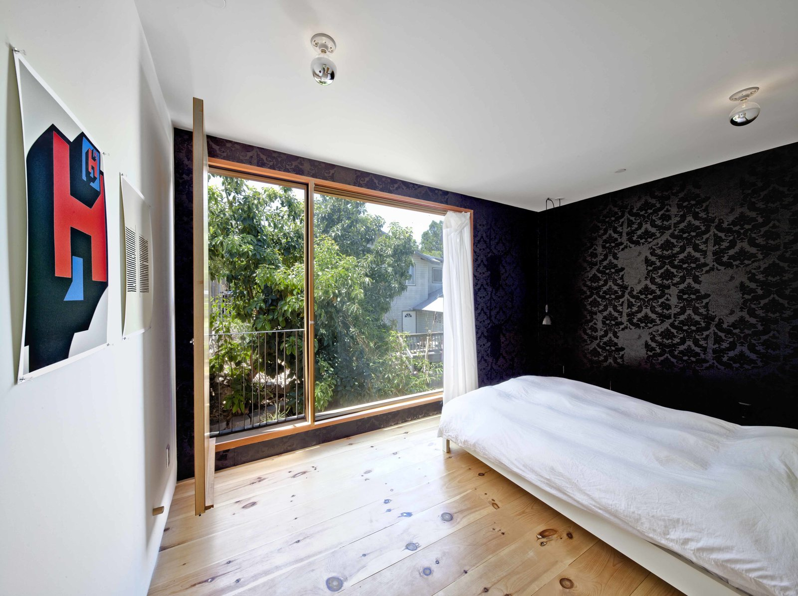 """The second story has two rooms and a bathroom. Storey uses the room overlooking the street as his architecture studio, and the quiet back room as a bedroom. Its small balcony is the height of the avocado tree canopy, giving him the sense that he sleeps in a tree.   The wallpaper is the architect's own design. """"The wallpaper is called Torn and Confused,"""" he says. """"It was originally designed to look like it was torn from the wall, exposing another layer of wallpaper underneath. I love the irony of using it on a new house.""""  Photo 6 of 9 in Home and Studio Maximizes Very Narrow Site in Echo Park"""