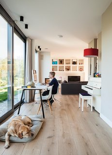 "Bram sits at a table by Gispen in the oak-floored public side of the house, facing the water, while the dog, Bommel, relaxes nearby. ""We really like the indoor-outdoor effect,"" says Bram's dad, Mark de Graaf. ""The ground floor opens on three sides—on a summer day, it stays cool."""