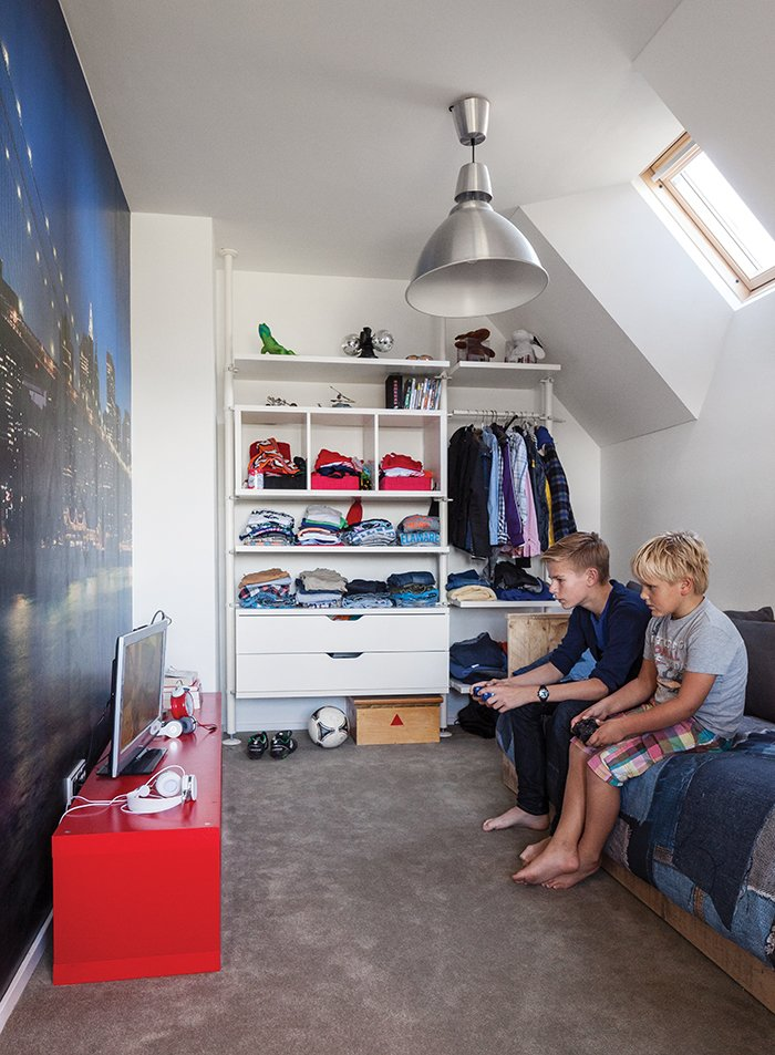 Kids Room, Bed, Bedroom Room Type, Shelves, Pre-Teen Age, Storage, and Boy Gender In a family's house in Amsterdam, a New York cityscape takes up one wall in Bram's room, which has furnishings from Ikea and a bed from Goed Gemaakt.  Photo 11 of 13 in A Modern Take on the Pitched-Roof