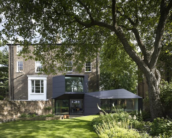 """Back Yard, Trees, Grass, Exterior, House, Metal, and Brick The roughly 5,000-square-foot Lens House renovation, which was finished in 2012 and just won a 2014 RIBA National Award, required six years, major remedial work on the roof and walls, approval from the planning committee, and even a sign-off from a horticulturalist to guarantee the backyard excavation didn't interfere with a walnut tree. """"These things aren't for people who are in a hurry,"""" says architect Alison Brooks. The focus is the ten-sided trapezoidal office addition. """"It wraps itself around the house with a completely different set of rules than the Victorian building,"""" she says.  Best Exterior Metal Trees Photos from Victorian Home in London Gets a Modern Office Addition"""