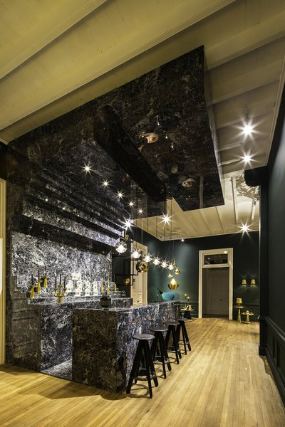 """The Bar Club is outfitted with what Dixon describes as a """"monolithic"""" bar holding his new Plum barware line."""
