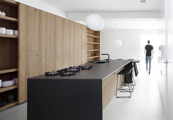 The smooth, raven-hued island in this kitchen is made of oak with a thin stone countertop. A Foscarini Gregg Pendant hangs overhead.