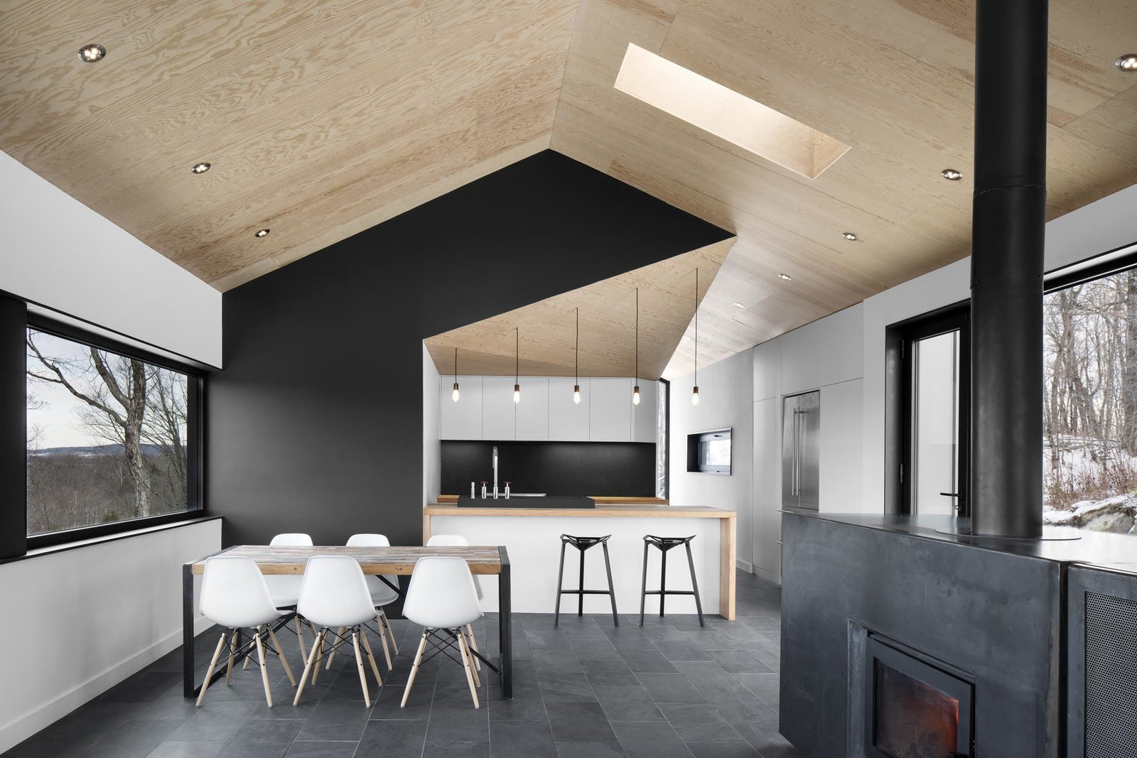 """Dining Room, Table, and Chair The architects stuck to a gray-scale color palette, installing slate tile floors that softly contrast with the white walls and Eames dining chairs. """"It lets the views out the windows become the focus,"""" Dworkind explains. Doses of pure black accent important features, like the central wall that divides the kitchen and master bedroom behind it from the main living space.  Best Photos from Amazing Cantilevered Home in the Mountains"""
