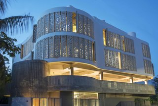 The petite hotel was built on the foundation of what formerly was a three-bedroom house. The striking exterior features a number of perforated panels made of glass reinforced concrete.