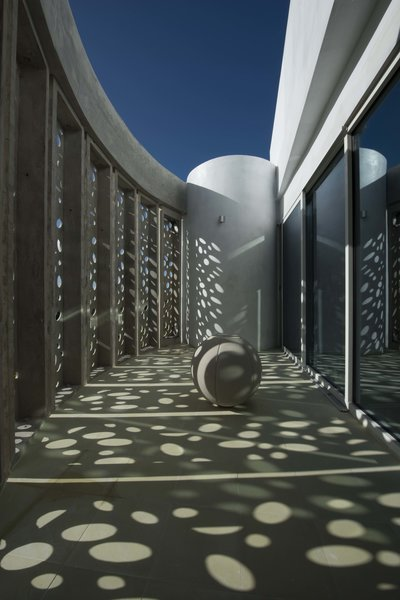 Behind the perforated shell lie balconies off the guest rooms. Some of them open up to the sky.