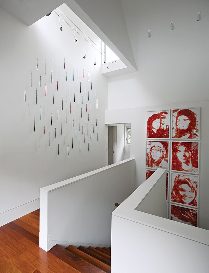 Staircase, Wood Railing, and Wood Tread In the stairwell hangs a series of 1999 Vik Muniz works that resemble Andy Warhol's iconic portraits of Jacqueline Kennedy Onassis, but are actually photographs of pooled ketchup.  Photo 6 of 8 in Read This Before You Hang Up New Artwork from Art-Filled Hamptons Vacation Home
