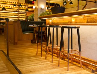 Upland's bar is topped with Calacatta Gold marble; the custom bar stools are in painted oak.