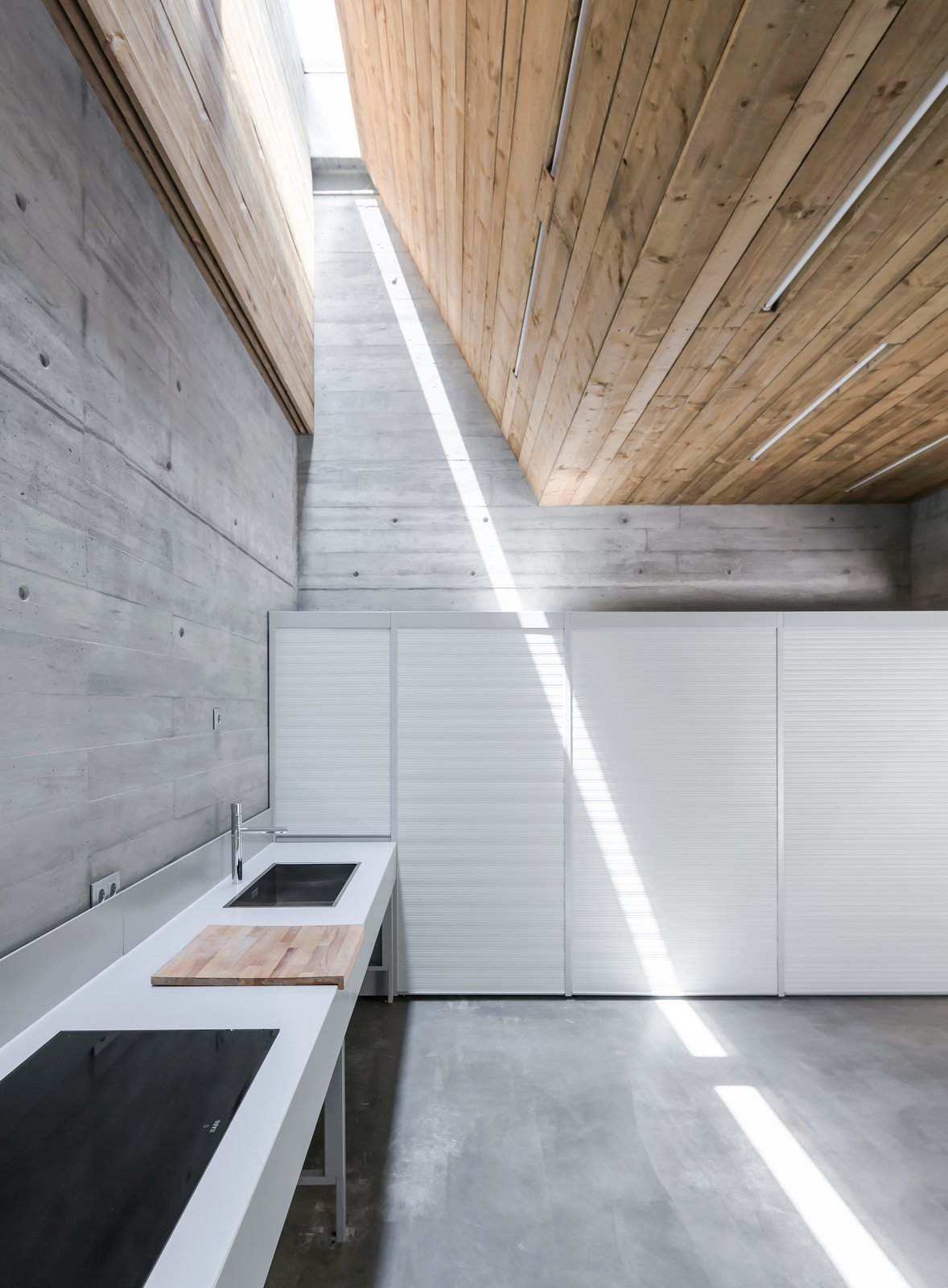 House in Matosinhos is a minimal home located in Matosinhos, Portugal, created by nu.ma.  The lot, where the house is inserted, has a non-regular shape, longitudinal, and perpendicular to the street Nossa Senhora da Conceição. It was important to keep the alignment of the house with the existing buildings in order to avoid formal irregularities within the street development. The interior spatial distribution is separated by function and by floors. Due to the longitudinal nature of the lot, the architects proposed an internal yard at the center of the home to allow for natural light to enter the dining/living room and kitchen.  Concrete from A Half-Buried Home Fights for Sunlight