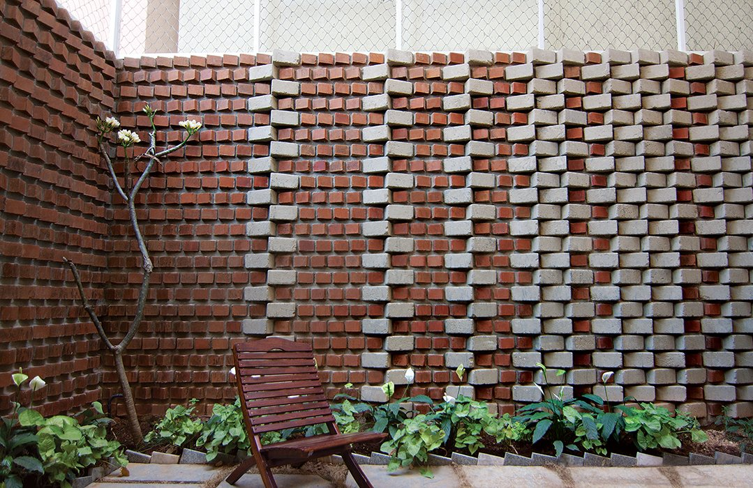 The wall surrounding Ravi and Esha Chowdhary's backyard in Bangalore, India, includes bricks made from soil that was excavated for their home's foundation.  Photo 1 of 3 in Inventive Garden Home in India