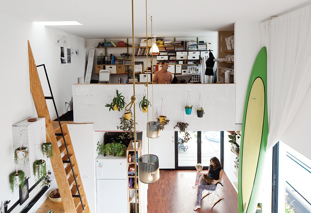 Office, Shelves, Medium Hardwood Floor, and Storage Designer and digital fabricator Shawn Benson shares his 595-square-foot second-floor space with his wife, Jessica, and their daughter, Roux. The 15-foot-high ceilings allow plenty of room for a full-size ocean paddleboard.  Photo 2 of 14 in San Diego Teaches Us How Micro-Living Can Thrive