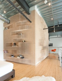 Merge Architects wrapped the peg wall around three sides of a bathroom to hide a door and provide a storage for books and knick knacks.