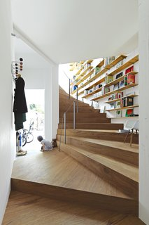 Bookshelves add extra utility to the undulating staircase in Tokyo's 921-square-foot Coil house. The space was designed by architect Akihisa Hirata for Sakura and Ryo Sugiura, a young couple with two children.