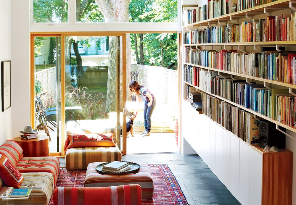 Living Room, Bookcase, Rug Floor, Sofa, Chair, Ottomans, and Slate Floor Architect Tamira Sawatzky used Ikea components—one-inch Lagan butcher block countertops and inexpensive Ekby Lerberg brackets—when designing the bookshelves along the living room wall in the home/studio he designed for himself and his wife in Toronto.  Best Photos from Tips for Maximizing Bookshelf Space