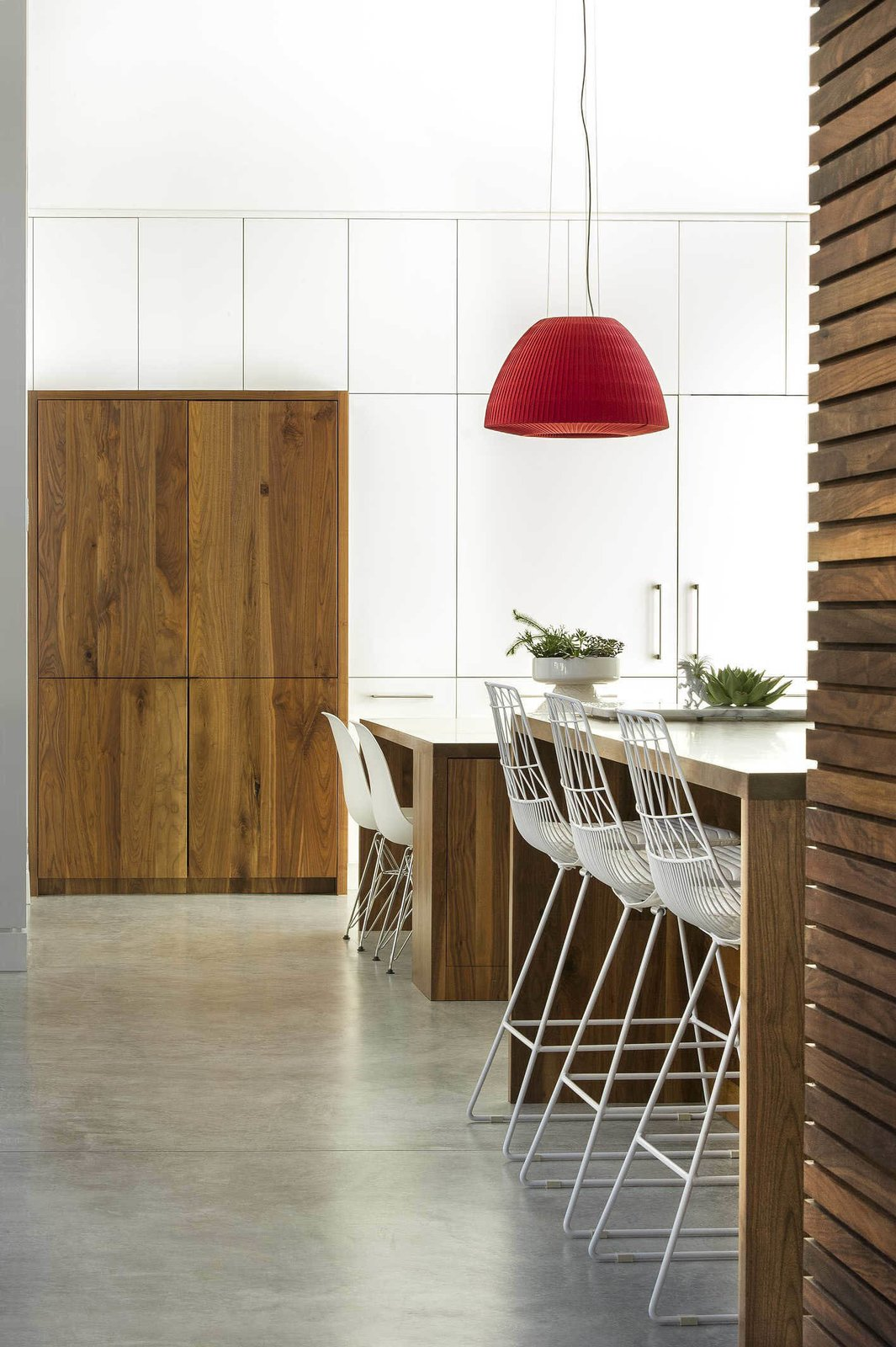 Kitchen, Concrete Floor, Pendant Lighting, and Wood Cabinet The floors in the kitchen are polished concrete.  Photo 5 of 7 in A Modern Home For a Design-Savvy Family in Florida