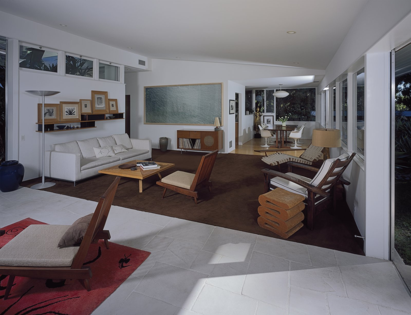 """Living Room The main space containing the living and dining area and kitchen was relatively unchanged. """"In consideration of the original vision, the additions blend with the original structure, and the basic idea of the open flow between the inside and the outside is maintained and reinforced in all areas,"""" the architect says.  Photo 5 of 6 in A Neutra Renovation in Los Angeles"""