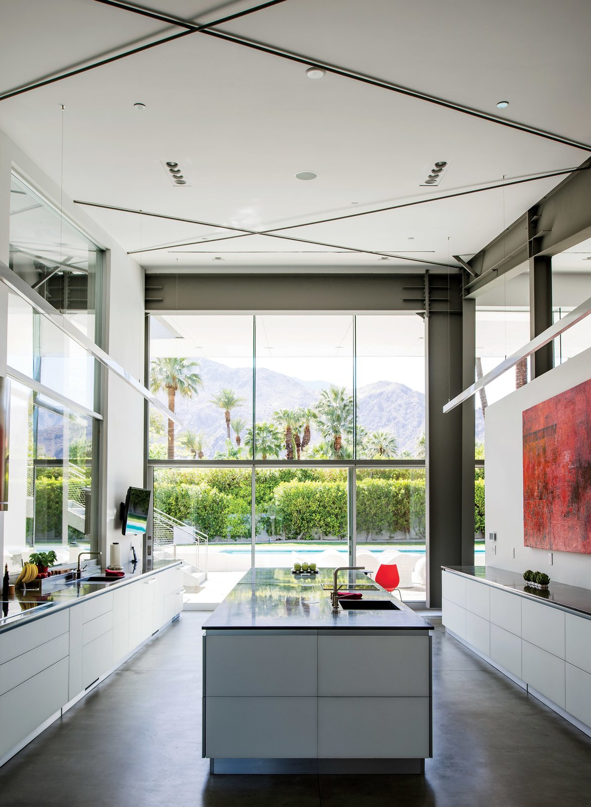 Kitchen, Ceiling Lighting, Concrete Floor, and Recessed Lighting In the kitchen, which faces west to capture views of the San Jacinto Mountains, a large red work by James Jensen punctuates one wall. The induction cooktop is from Gaggenau; the sinks were sourced from Blanco.  Hä from An Energy-Efficient Hybrid Prefab Keeps Cool in the Palm Springs Desert
