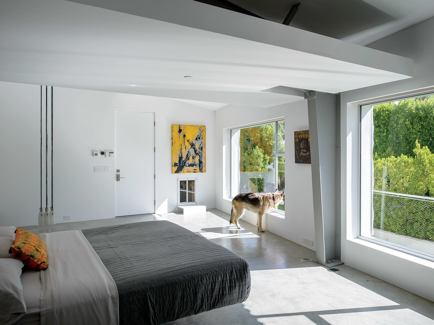 Bedroom, Concrete Floor, and Bed In the master bedroom, a Droog Milk Bottle lamp hangs next to a Fluttua Bed designed by Daniele Lago. An artwork by Brooke Westlund hangs over a custom pet door for the client's dog, Kona.  Photo 2 of 25 in Leap Into the Year of the Dog With These 25 Pups in the Modern World from An Energy-Efficient Hybrid Prefab Keeps Cool in the Palm Springs Desert