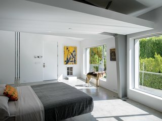 In the master bedroom, a Droog Milk Bottle lamp hangs next to a Fluttua Bed designed by Daniele Lago. An artwork by Brooke Westlund hangs over a custom pet door for the client's dog, Kona.