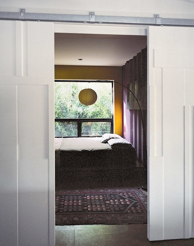 Bedroom, Bed, and Floor Lighting Though many of the interior surfaces have been spray-foam insulated and covered in Sheetrock, the couple, drawn to the natural patina of the shipping containers, opted to keep select areas of the material exposed. Closed off by bas-relief doors designed by Mathesius, the main guest room is one of few spaces that put whole walls of the raw surface on display, painted in Benjamin Moore's warm Kalamata and Wasabi hues. benjaminmoore.com  Photo 11 of 12 in A Shipping Container Home in Pennsylvania Embraces Its Rugged Industrial Origins