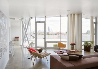 The floors are polished concrete, a money-saving move that allowed for splurges like the floor-to-ceiling windows from Chicago Tempered Glass set in Tubelite frames.