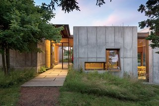 Despite being set in concrete, an idyllic modular retreat is built to go with the flow. When husband and wife Tarek and Cynthia decided that their aging home on Martha's Vineyard needed to be completely replaced, they began a long search for an architect who not only would deliver a successful collaboration, but also lived on the island. It was not a small order, but serendipity—and some sleuthing—eventually played its role. Large, dramatic openings bring transparency and contrast to the 10-inch-thick concrete facade, framing perspectival views of the landscape.