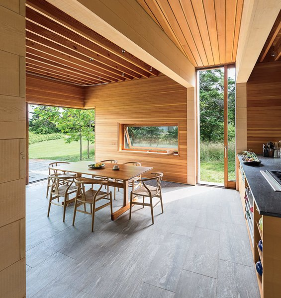 Douglas fir and Alaskan cedar richly line the interior walls, and the flooring is made of Vermont slate. In the kitchen and dining area, a group of Wishbone chairs by Hans Wegner for Carl Hansen & Søn surrounds a table by local furniture maker Larry Hepler.