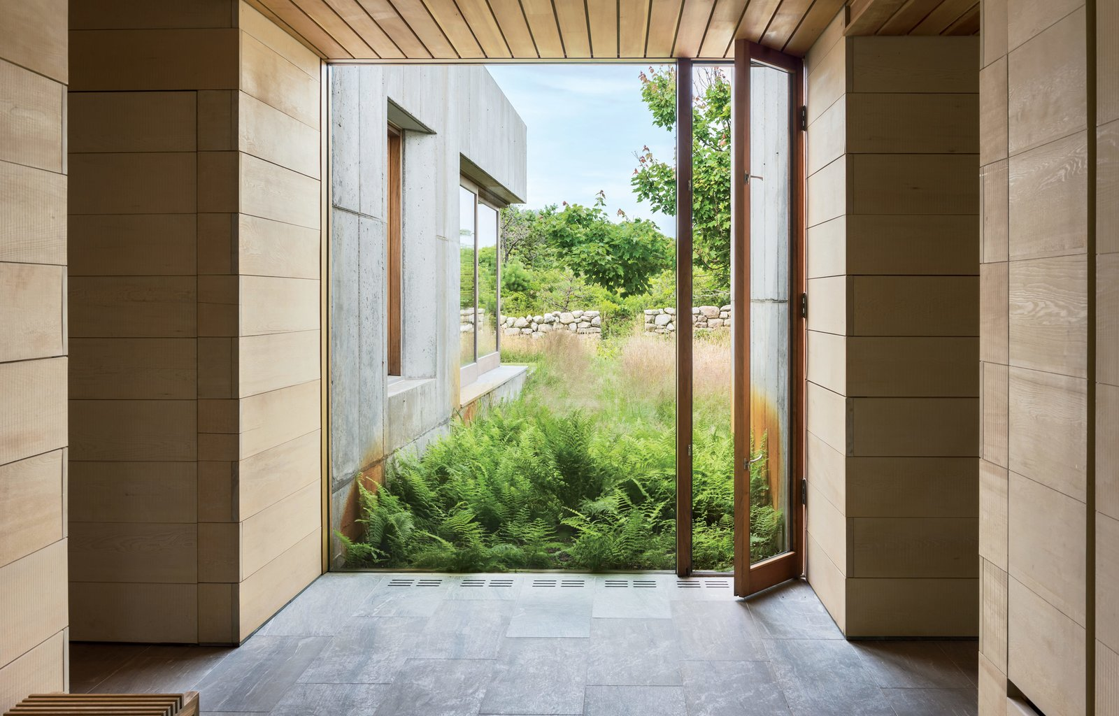 Doors, Folding, Exterior, and Wood An attentive sensitivity to site played into nearly every aspect of both the exterior andinterior spaces of the home. Architect Peter Rose collaborated with landscape architect Michael Van Valkenburgh, who worked to craft and maintain the wild, organic feel of the environs. Will Parry, a local builder, custom-fabricated all of the sustainably harvested Spanish cedar-and-glass windows and skylights throughout. Here, a vertical-swinging window at the end of the entry hallway opens directly to a lush expanse of vegetation.  Best Doors Wood Exterior Photos from Six Concrete Boxes Make a Jaw-Dropping Martha's Vineyard Home