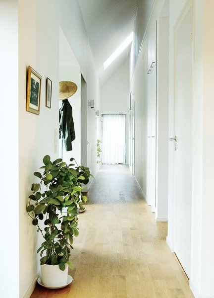 A double-height corridor runs the length of the house, and a slatted wall on the second floor overlooks the space.