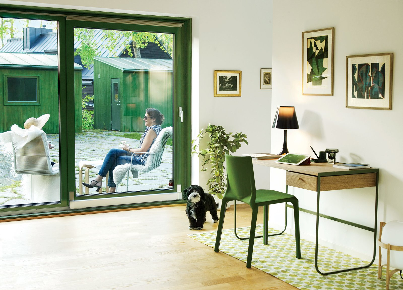 "Living Room, Chair, Light Hardwood Floor, Table Lighting, Rug Floor, Lamps, and Desk Franson Wreland also designed the court-yard and a pair of 160-square-foot outbuildings—one is used as guest quarters and the other as storage space. While residents Julia and Fatima Olivero-Reinius chat outdoors, Chippie the dog approaches an Asplund desk and a chair by LucidiPevere.  Search ""11plus world desk clock"" from This Bright Green Prefab in Sweden Looks Just Like a Monopoly House"