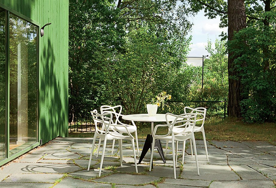 Outside, Kartell Masters chairs surround a Tom Dixon Screw table. Tagged: Outdoor, Large Patio, Porch, Deck, and Concrete Patio, Porch, Deck.  Photo 5 of 12 in This Bright Green Prefab in Sweden Looks Just Like a Monopoly House