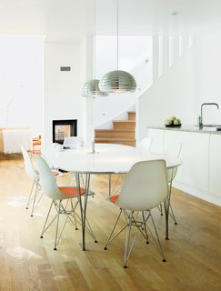 In the dining area, Splügen Bräu pendant lamps for Flos hang over a Super-Elliptical table by Piet Hein and Bruno Mathsson for Fritz Hansen.