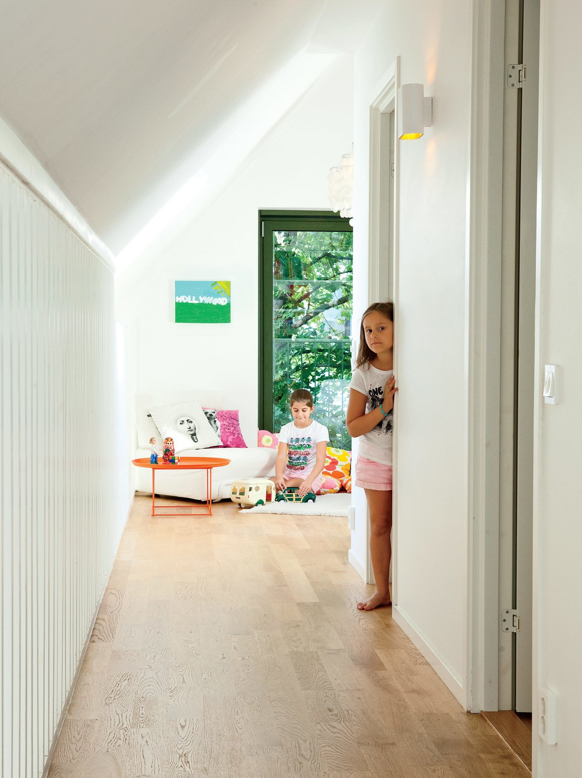 Kids Room and Bedroom Room Type The second floor holds three bedrooms and a living area for the girls. Here, Paula, 11, and Sofia, 9, hang out near an IKEA PS 2012 sofa by Nike Karlsson. The slatted wall at left allows a view to the downstairs.  Best Photos from This Bright Green Prefab in Sweden Looks Just Like a Monopoly House